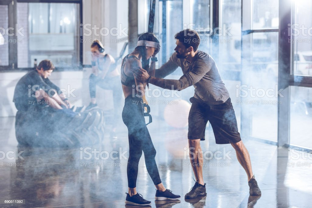 side view of man cheering up sportive woman in gym with trx equipment stock photo