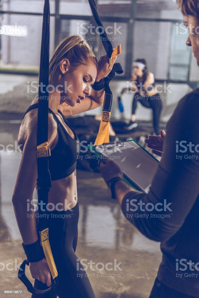 side view of man helping sportive woman exercising with trx gym equipment stock photo