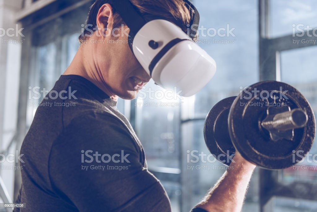 side view of man in virtual reality headset exercising with dumbbell in gym stock photo