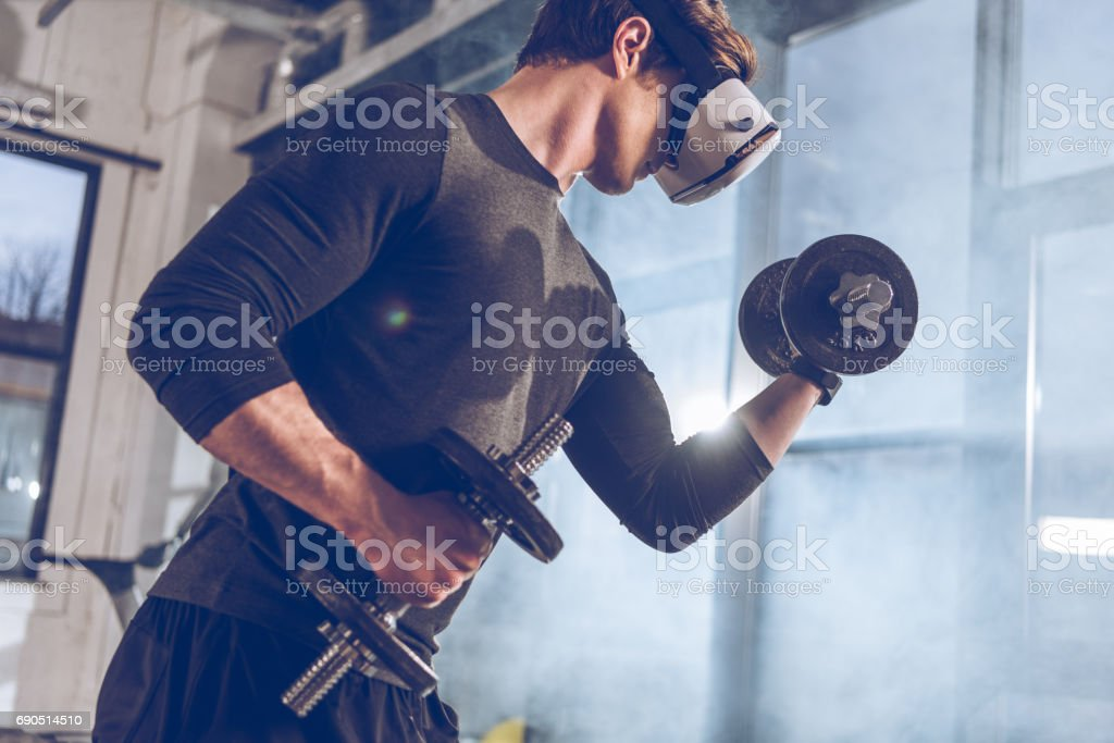 side view of man in virtual reality headset exercising with dumbbells in gym stock photo