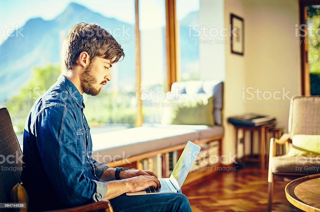 Side view of man using laptop on chair at home stock photo