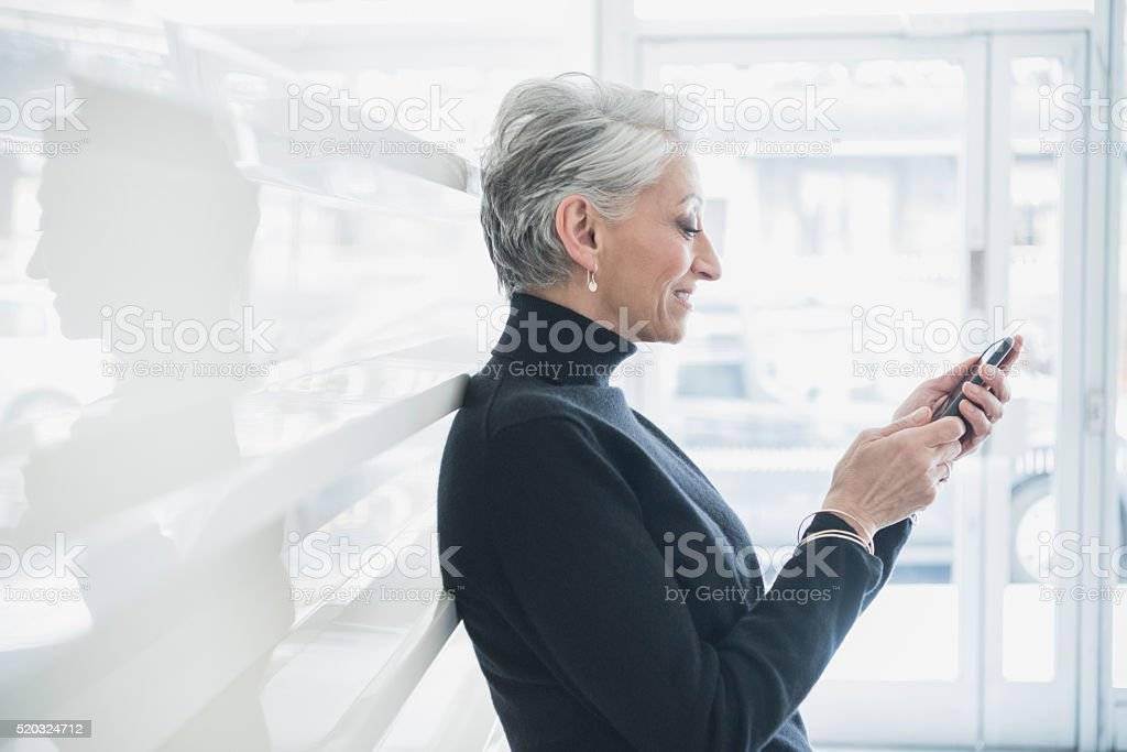 Side view of mature businesswoman using smartphone stock photo