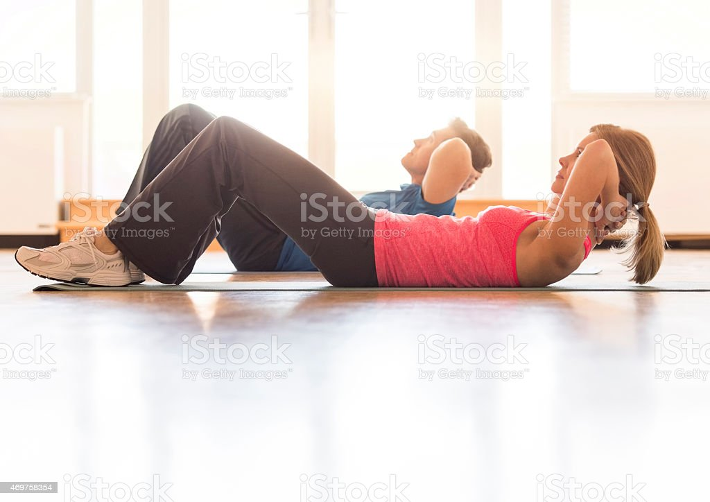 Side view of mature couple practicing sit-ups at home stock photo