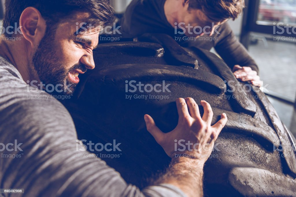 side view of men pulling tire together while exercising at the gym stock photo