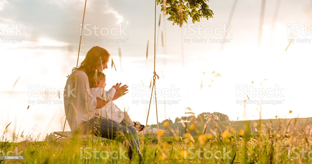 Side view of mother and daughter swinging on field stock photo