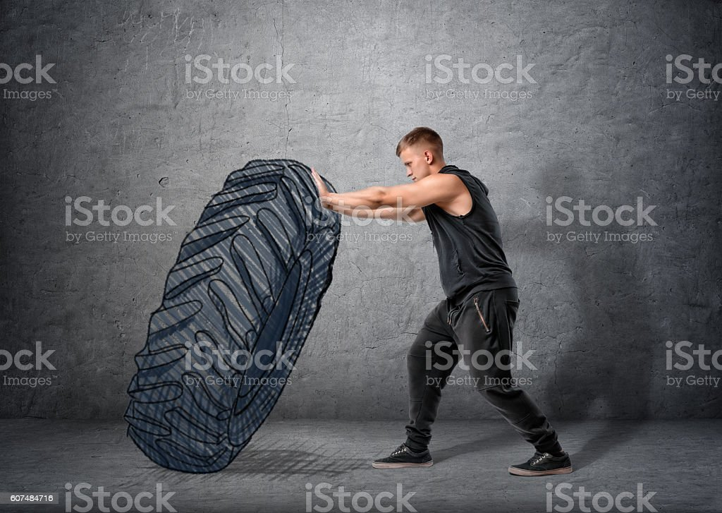 Side view of muscled young man pushing drawn tire to stock photo