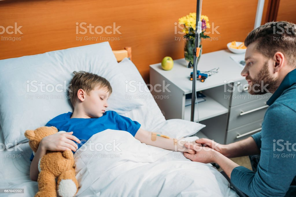 side view of pensive dad sitting near sick son with drop counter in hospital bed stock photo