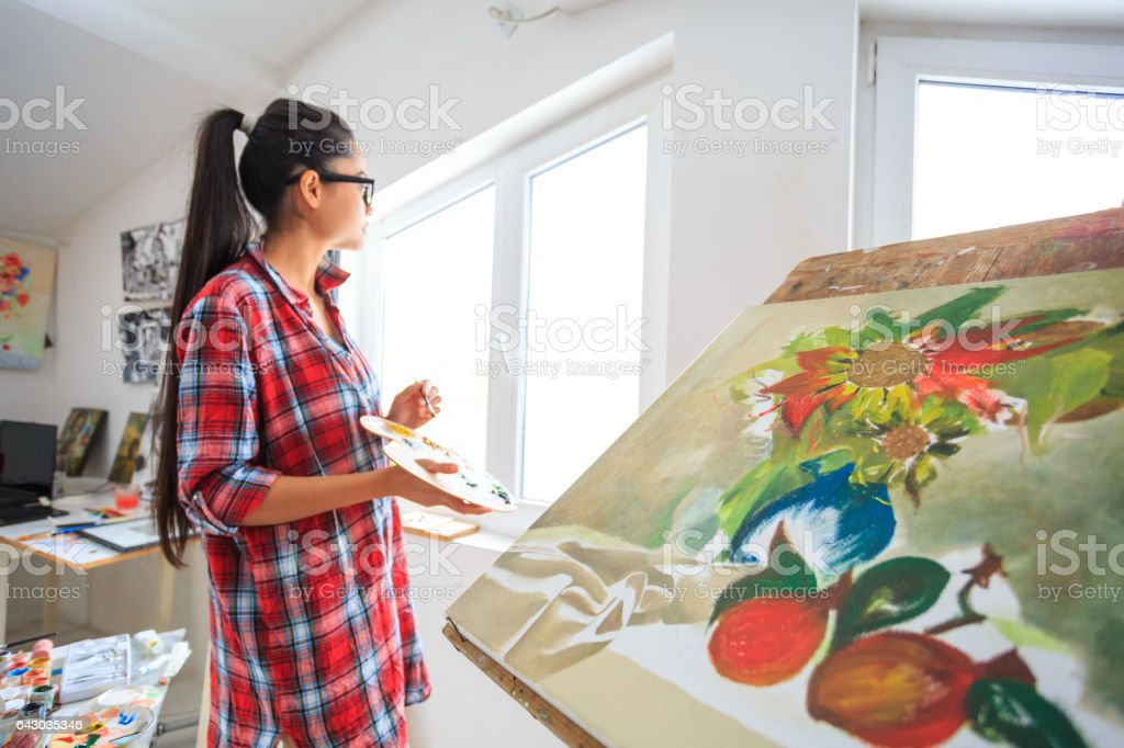Side view of pensive female artist working in sunny atelier stock photo