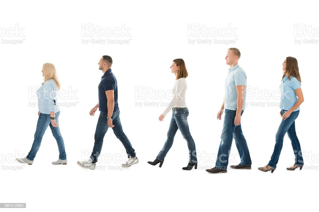 Side View Of People Walking In Queue stock photo