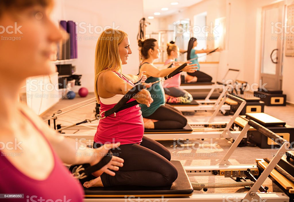Side view of pregnant women exercising on Pilates machine. stock photo