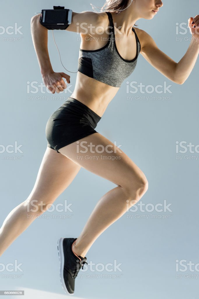 side view of running sporty woman on grey stock photo