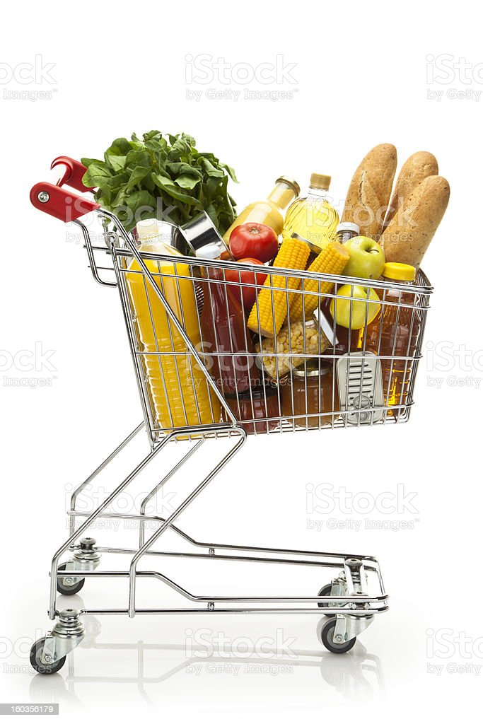 Side view of shopping cart filled with groceries and vegetables stock photo