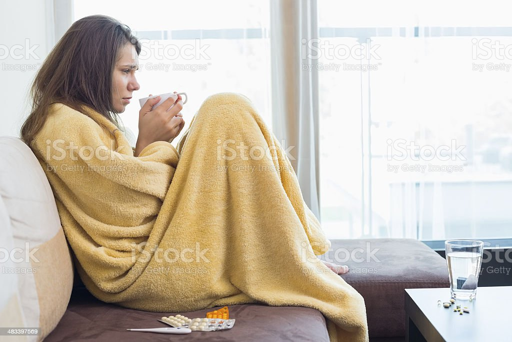 Side view of sick woman having coffee stock photo