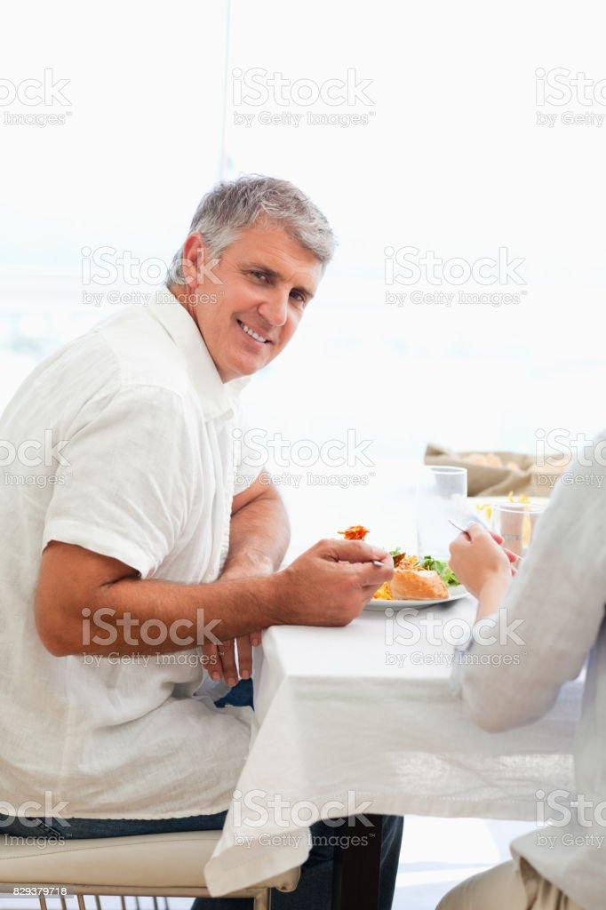 Side view of smiling man having dinner stock photo