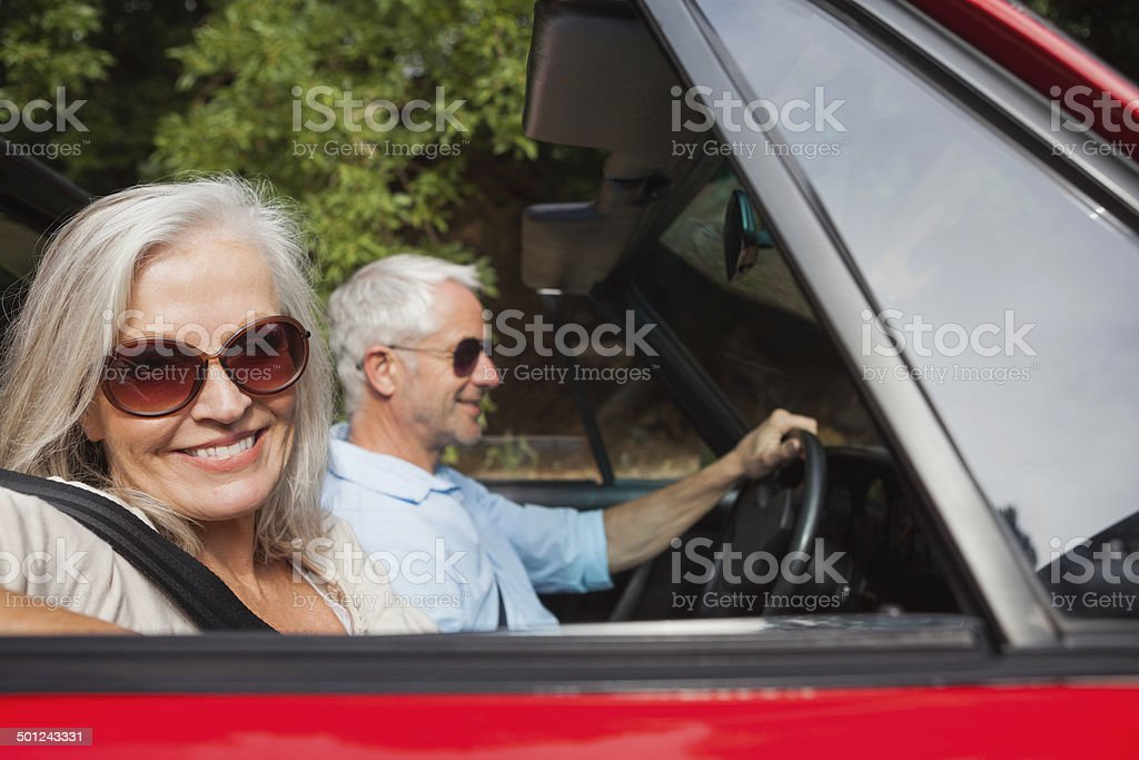 Side view of smiling mature couple driving red cabriolet stock photo