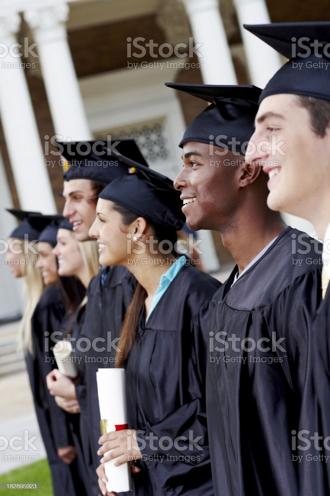 Side view of smiling young graduates standing in a line royalty-free stock photo