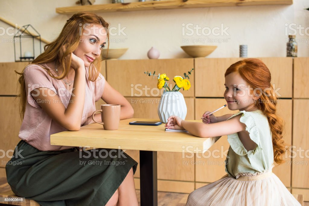 side view of smiling young mother looking at cute little daughter drawing with pencil in cafe stock photo