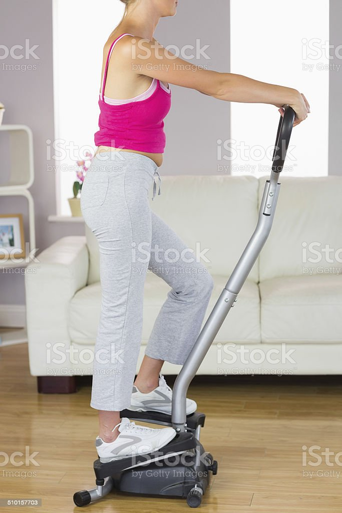 Side view of sporty woman training on step machine stock photo