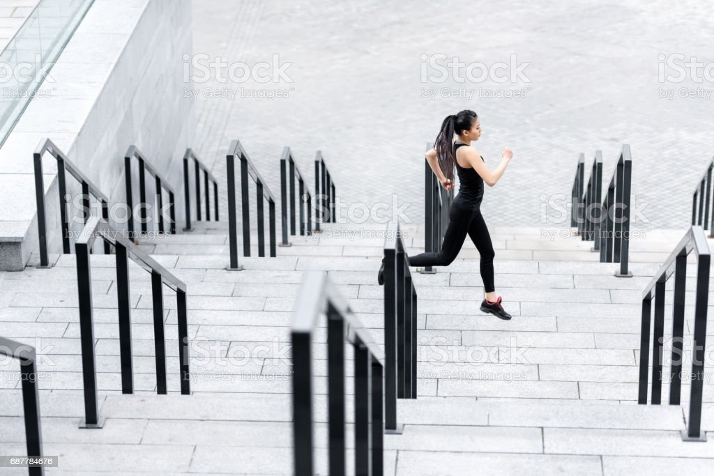Side view of sporty young woman jogging on stadium stairs stock photo