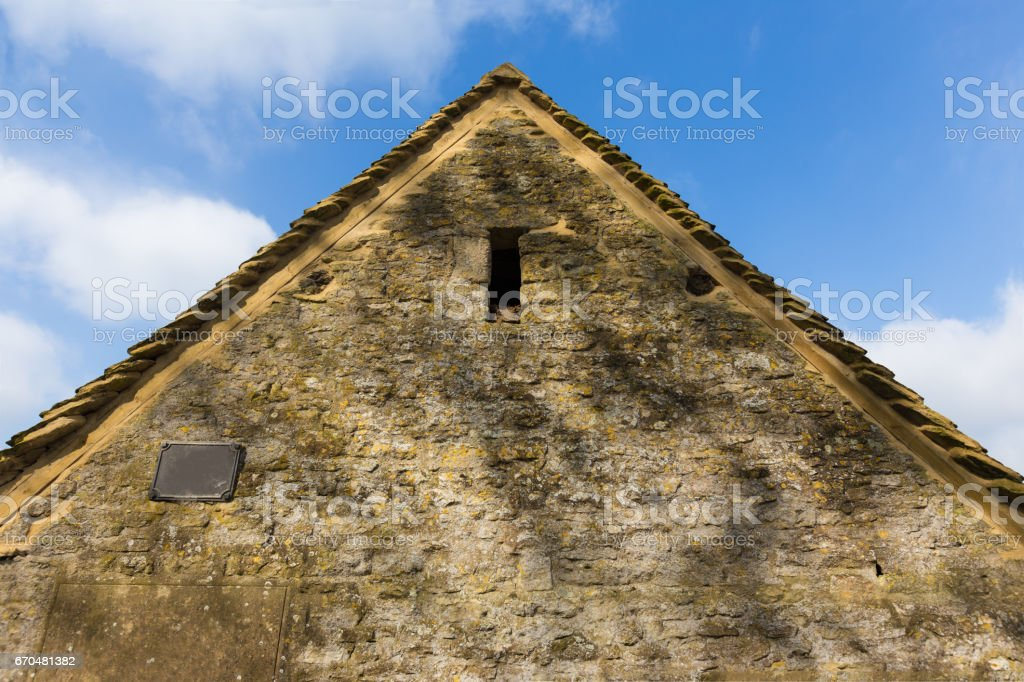 side view of stone wall house in Cotswold, England against blue sky with fluffy clouds stock photo