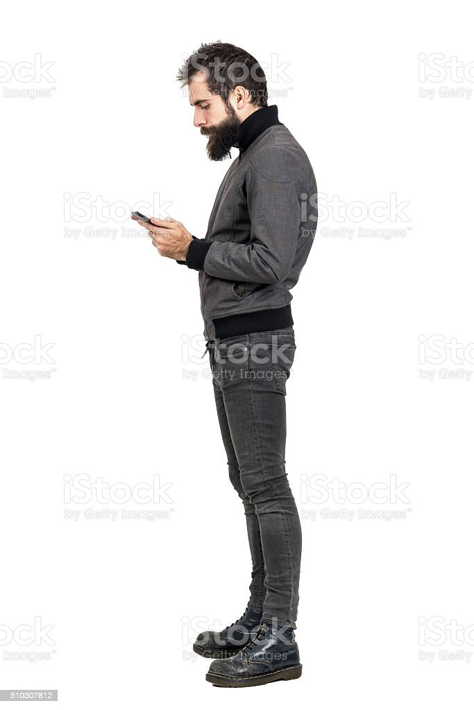Side view of stylish bearded hipster typing on his smartphone. stock photo