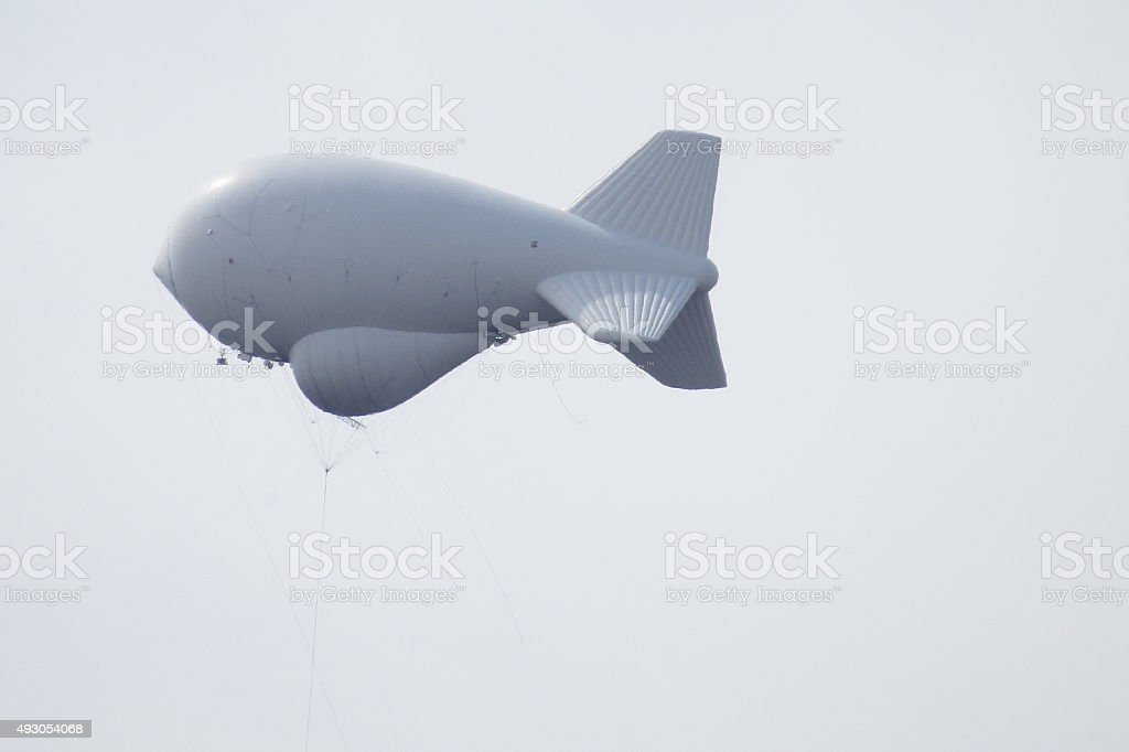Side View of Surveilance Aerostat in Grey Sky stock photo