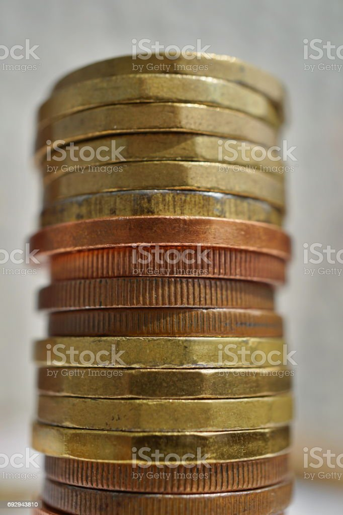 Side view of tall pile of metal coins in golden and copper color in front of silver background stock photo