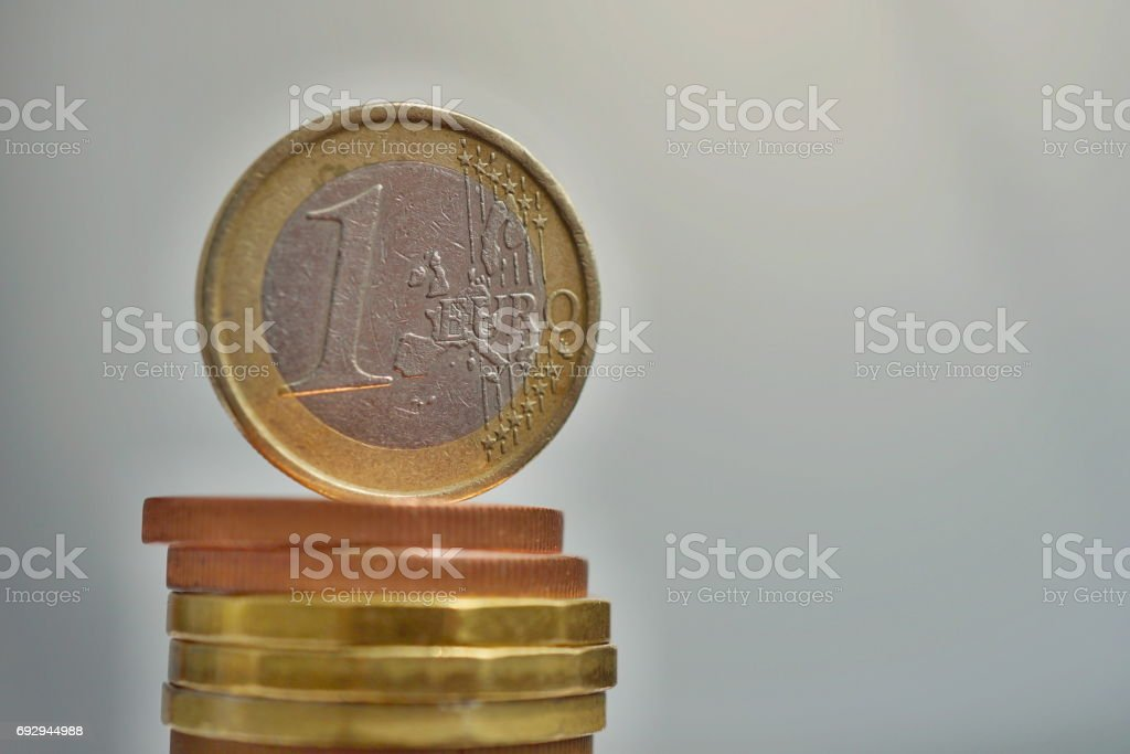 Side view of tall pile of metal coins in golden and copper color in front of silver background with one Euro (European currency EUR) coin on the top stock photo