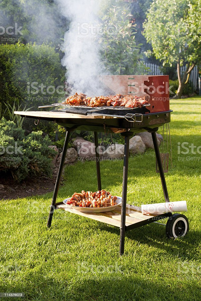 Side view of the smoking grill with meat stock photo