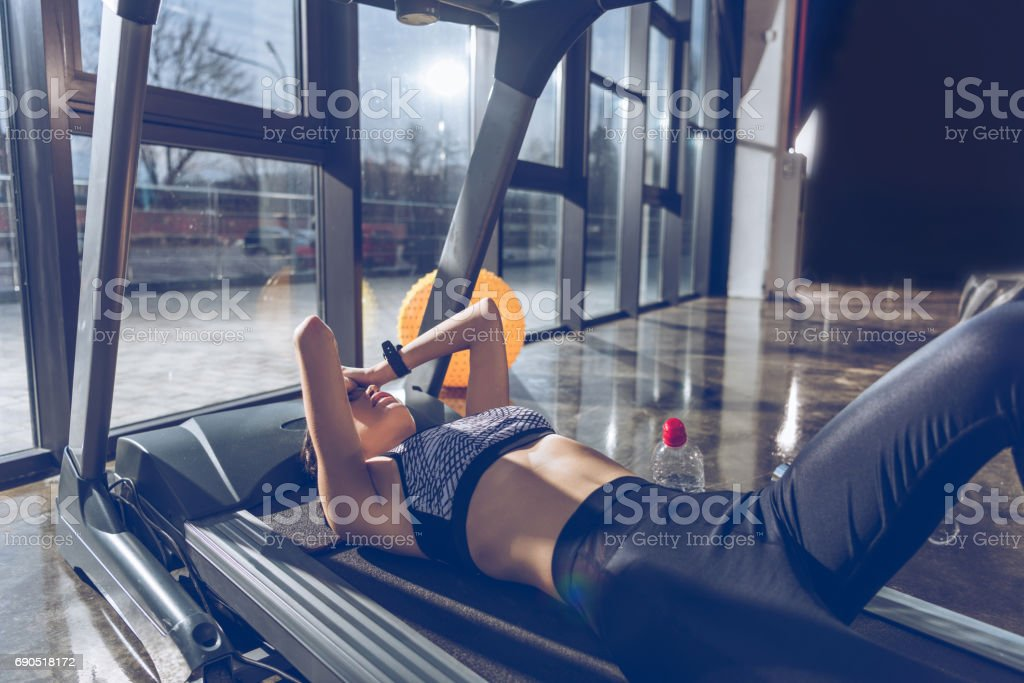 side view of tired sportive woman lying on treadmill in gym stock photo