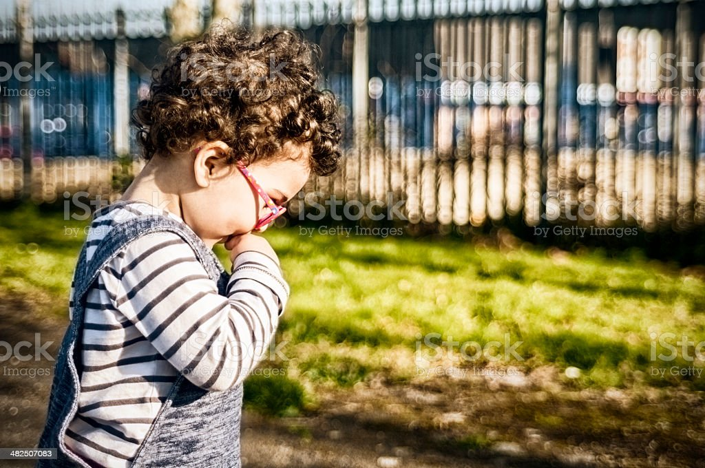 PEOPLE: Side View Of Toddler (2-3) With finger In Mouth. stock photo