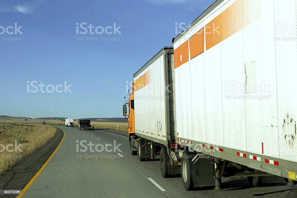 Side view of truck driving behind other trucks on highway stock photo