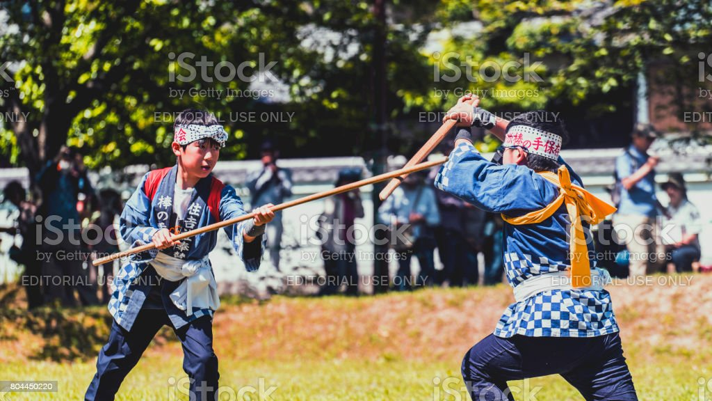 Side view of two boys fighting by bokuto in a field stock photo