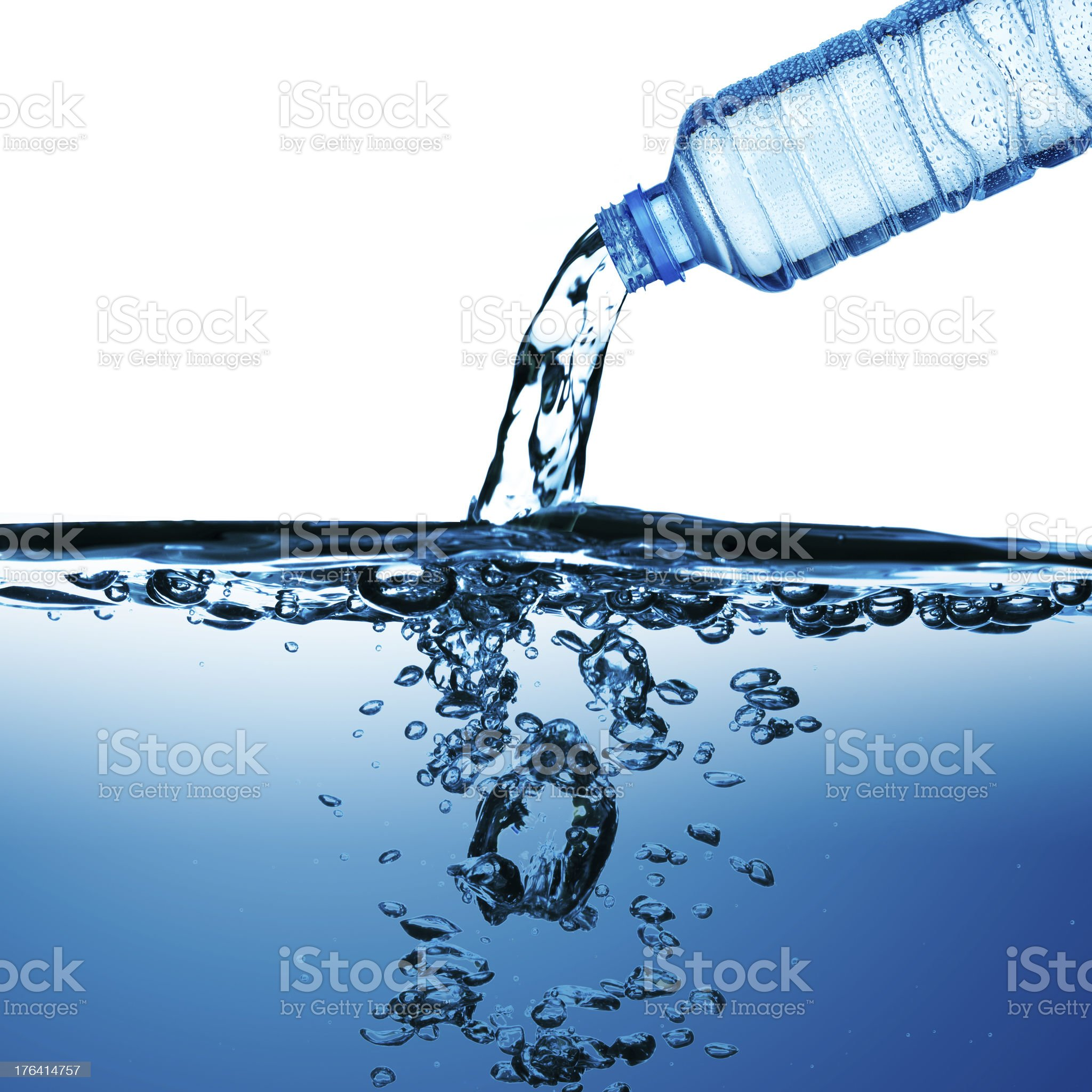 Side view of water pouring from bottle into clear tank royalty-free stock photo