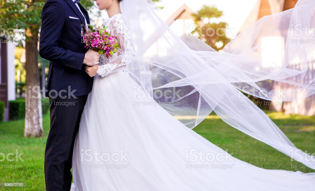 Side view of wedding couple standing at lawn stock photo