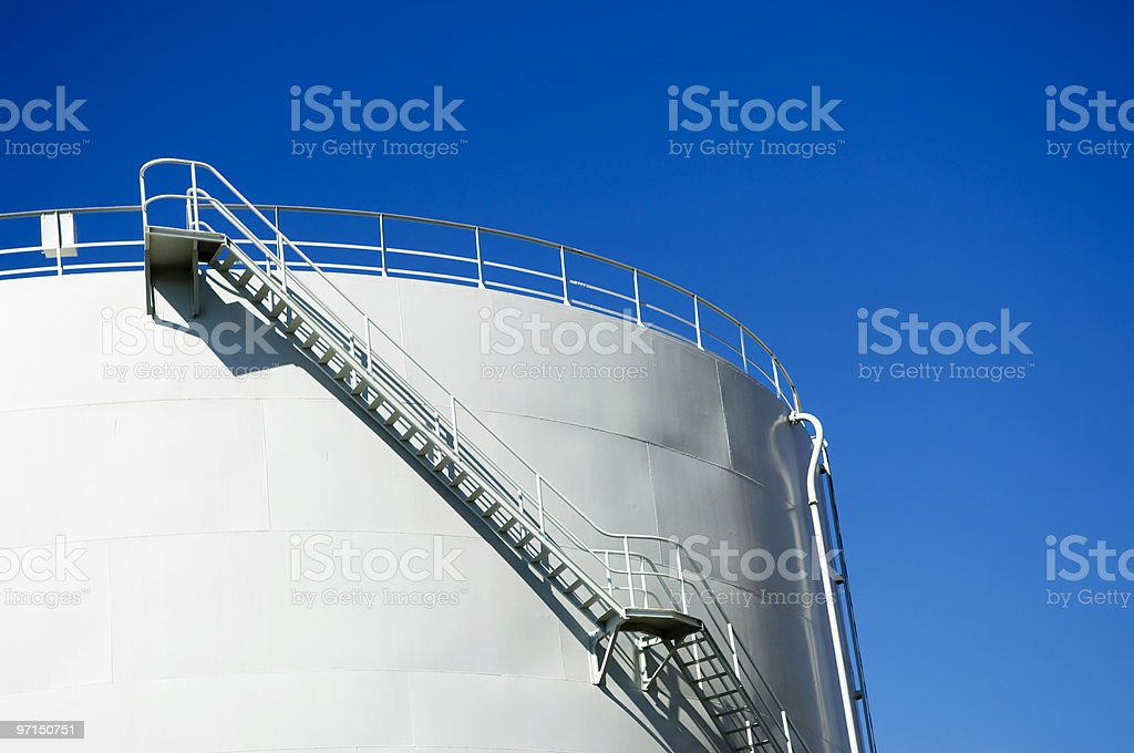 Side view of white oil reservoir against bright blue sky royalty-free stock photo