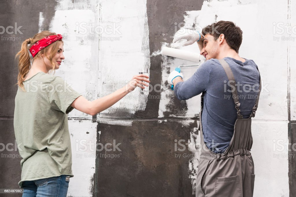 side view of woman brought working man glass of water stock photo