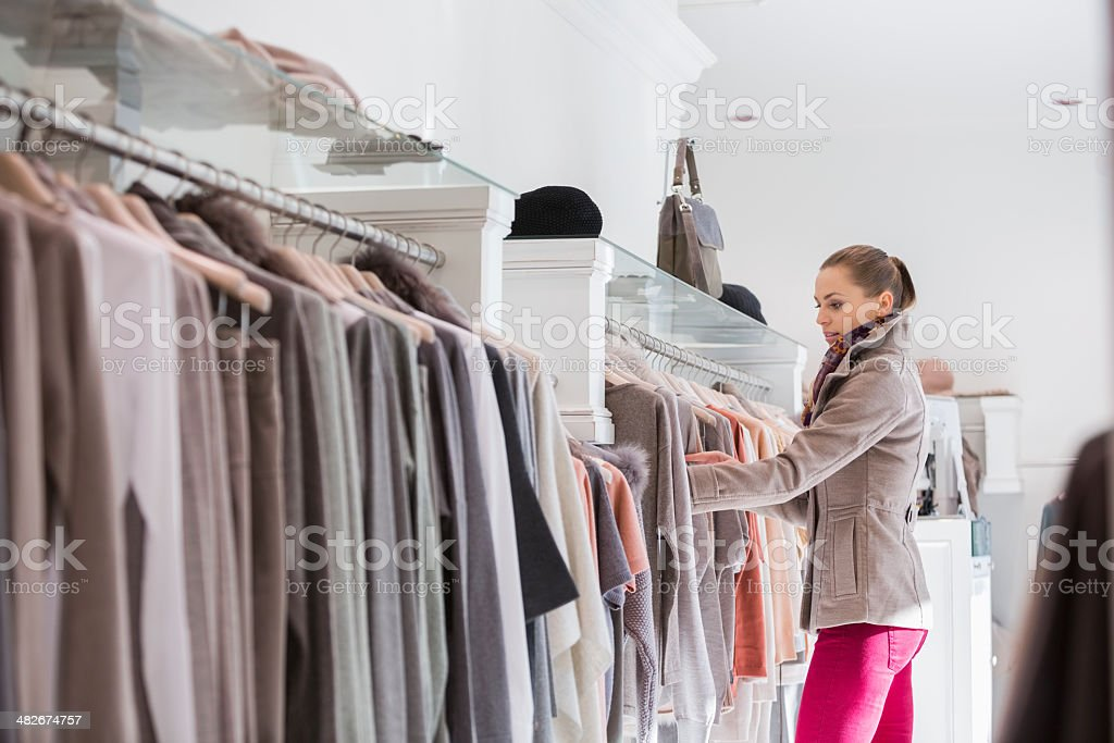 Side view of woman choosing sweater in store stock photo