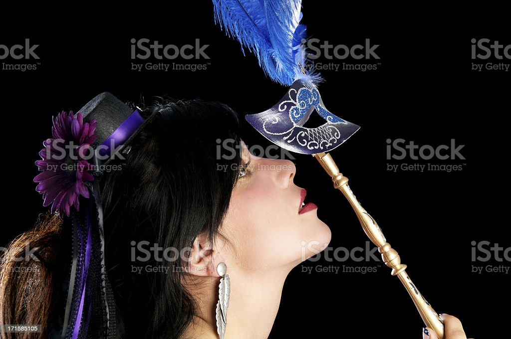 Side view of woman holding mask above face. stock photo