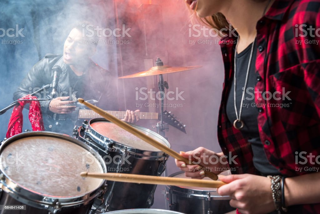 side view of woman playing drums and man singing into microphone, rock and roll band concept stock photo