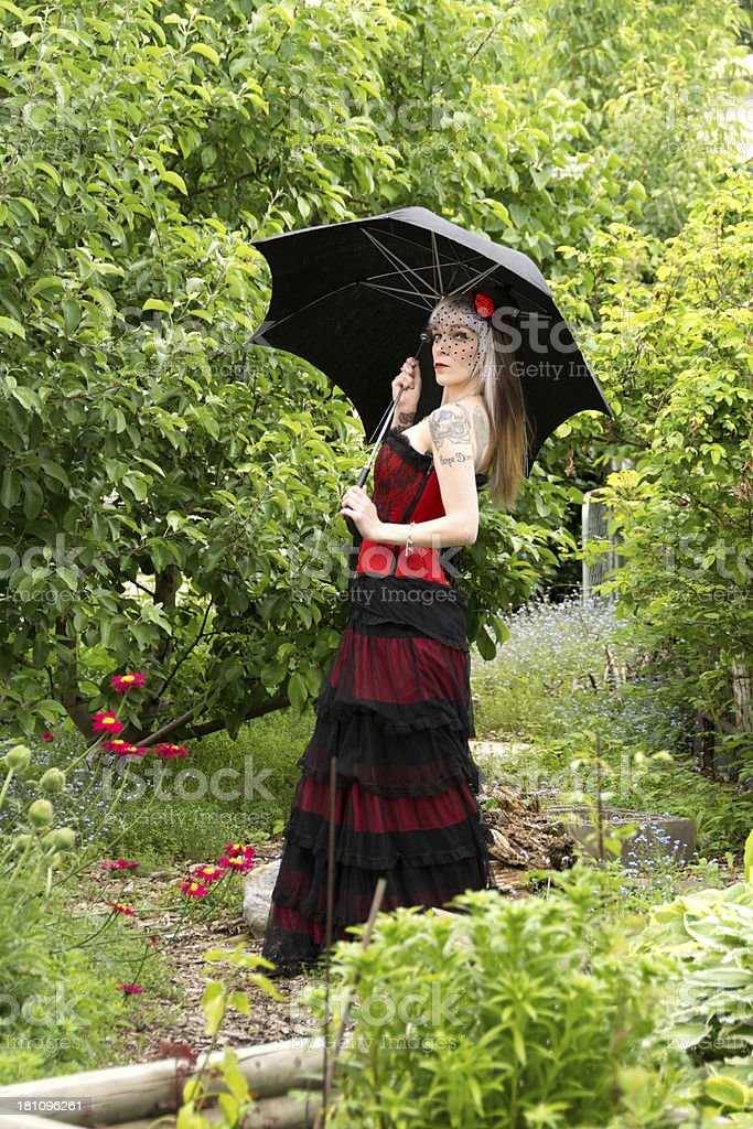 Side view of woman with black umbrella in garden. royalty-free stock photo