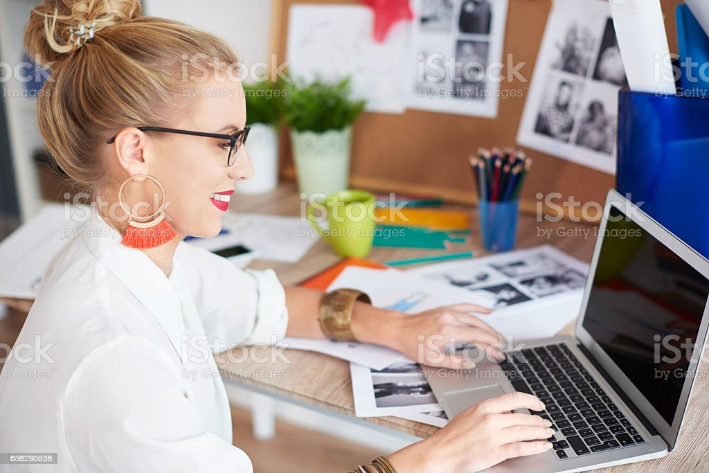 Side view of woman working with laptop at home stock photo
