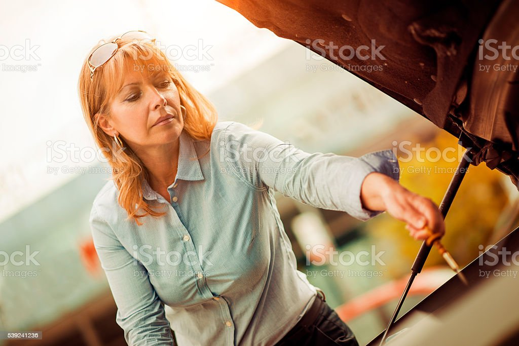 Side view of women checking motor oil stock photo
