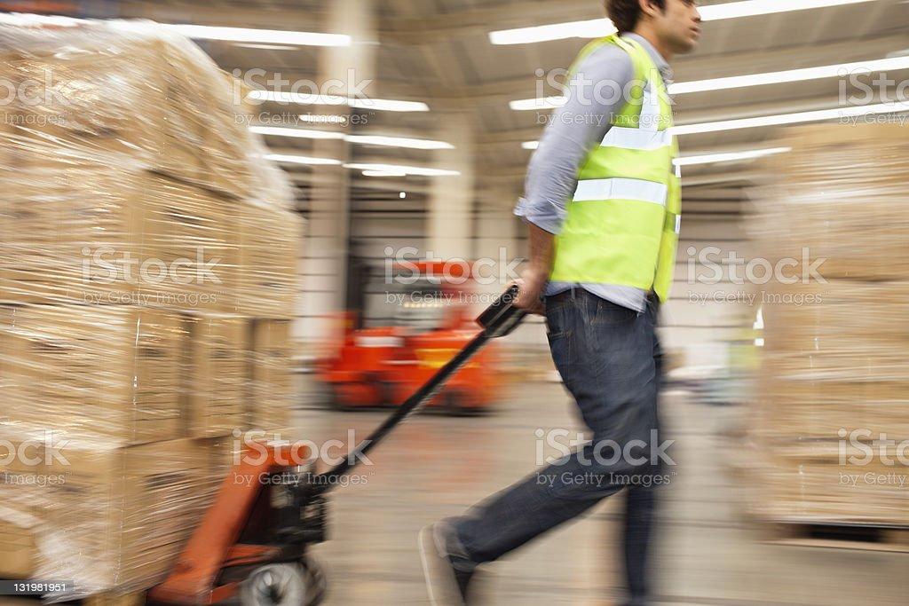 Side view of worker pulling packed cardboard boxes on push cart through warehouse royalty-free stock photo