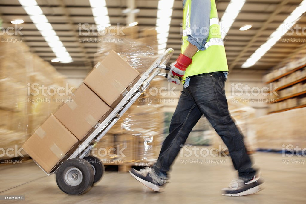 Side view of worker pushing trolley of cardboard boxes through warehouse stock photo