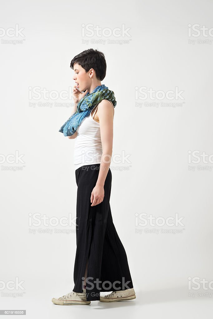 Side view of young beauty talking on the phone. stock photo