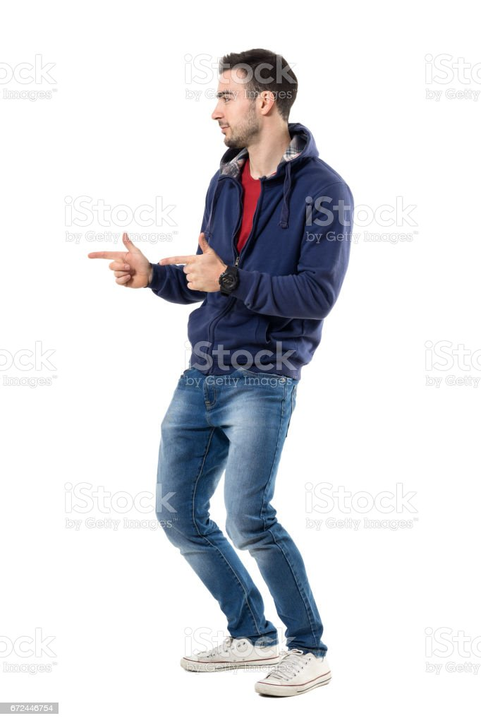 Side view of young casual guy pointing finger showing pistol hand gesture stock photo