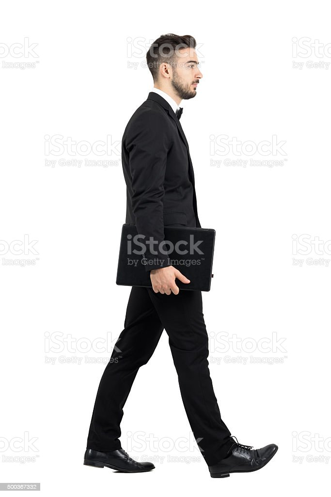 Side view of young executive carrying laptop walking stock photo