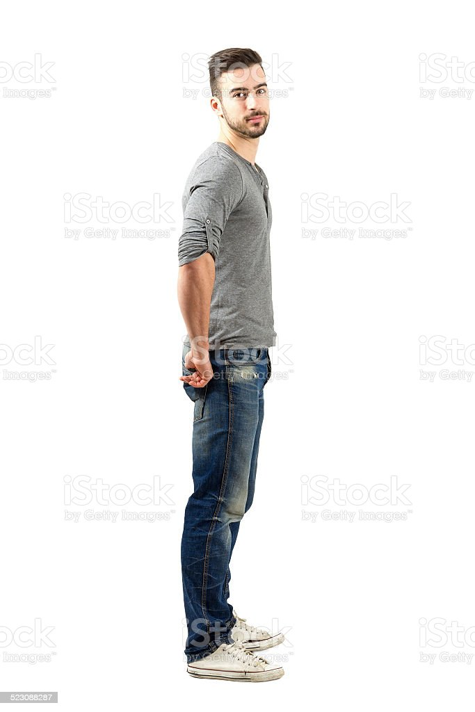 Side view of young fit guy in jeans and sneakers stock photo