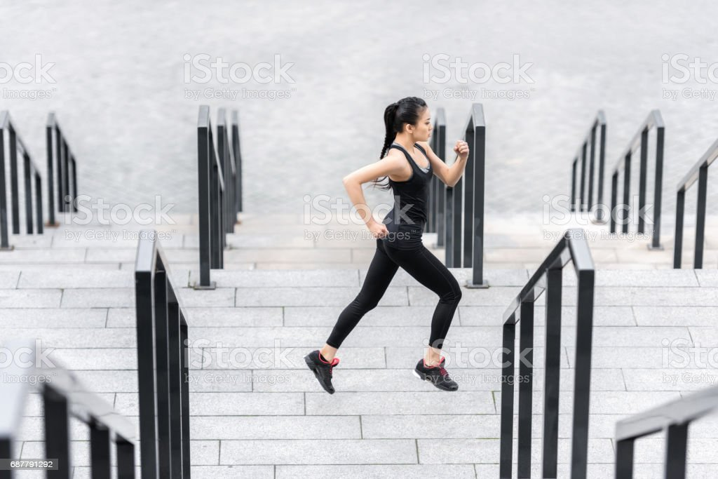 Side view of young fitness woman in sportswear training on stadium stairs stock photo